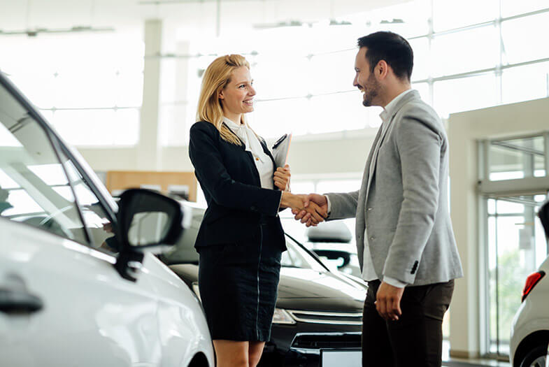 saleswomen shaking a mans hand in a prestige car showroom