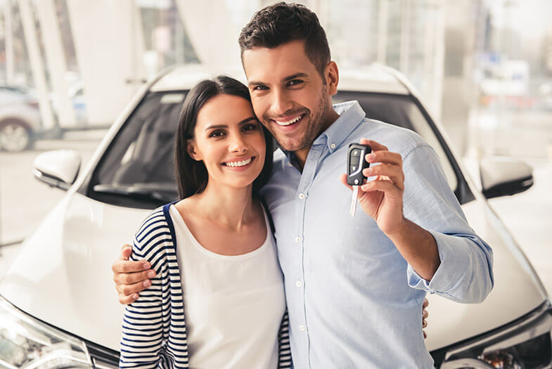 young couple holding up key to their new car