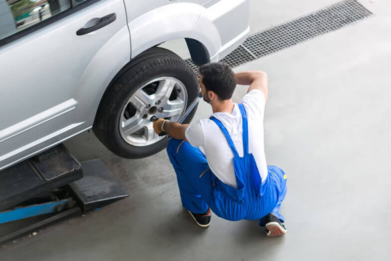 mechanic chanding a car tyre in a service centre