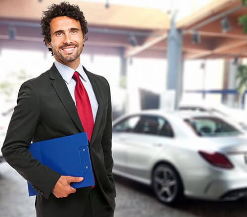 smiling car salesman holding a folder